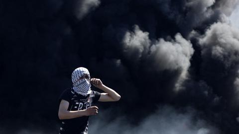 Ein vermummter Palästinenser steht im Gazastreifen vor schwarzen Rauchschwaden. (AFP)
