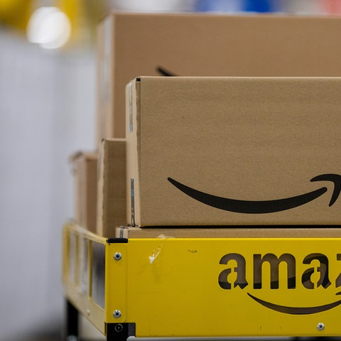 Pakete mit Amazonlogo liegen auf einem Wagen. (dpa)