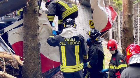 Feuerwehrleute klettern in die abgestürzte Gondel (dpa)