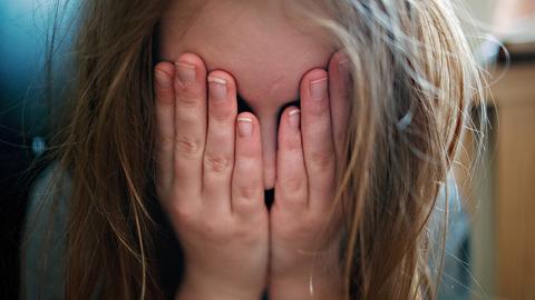 Ein Mädchen bedeckt ihr Gesicht mit den Händen (dpa)