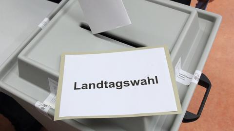 Ein Stimmzettel wird am 13.03.2016 in einem Wahllokal zur Landtagswahl in Magdeburg (Sachsen-Anhalt) in eine Urne gesteckt. (dpa)