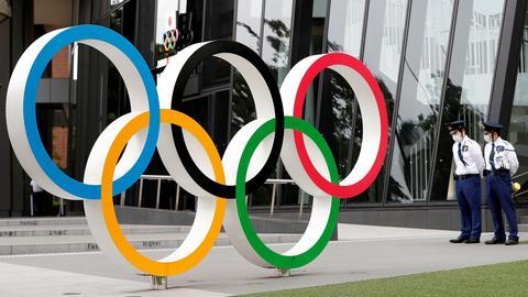 Sicherheitspersonal steht neben den olympischen Ringen vor dem Hauptquartier des japanischen Olympischen Komitees in Tokio (Japan). (REUTERS)
