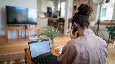 Eine Frau nimmt wegen des Coronavirus aus ihrem Wohnzimmer an einer Telefonkonferenz teil ()