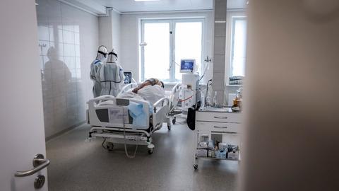 Ärzte in Schutzkleidung betreuen einen Patienten auf einer Intensivstation für Covid-19-Patienten in Moskau. (dpa)