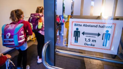 Schüler betreten eine Schule mit Hinweisschild auf die Corona-Regeln an der Tür. (dpa)
