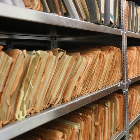 Eine Mitarbeiterin des Stasi-Museums steht im Stasi-Archiv zwischen Regalen mit bisher nicht erfassten Unterlagen. (dpa)