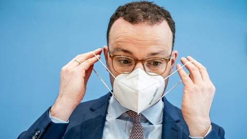 Jens SPahn setzt sich eine Maske auf (dpa)