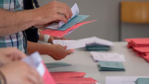 Wahlhelfer und Wahlhelferinnen öffnen im Klassenzimmer einer Schule in Magdeburg die Umschläge der Briefwahl. (dpa)