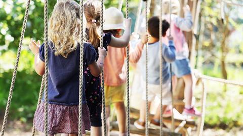 Kinder laufen in einer Kita über eine Hängebrücke. (dpa)