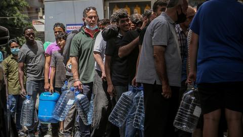 Menschen mit Plastikgallonen warten in der Schlange an einer Tankstelle in Beirut.  (dpa)