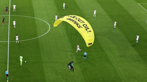 Ein Greenpeace-Aktivist landet auf dem Spielfeld  (dpa)
