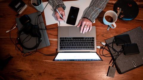Eine Frau sitzt mit einem Laptop an einem Tisch im Homeoffice. (dpa)