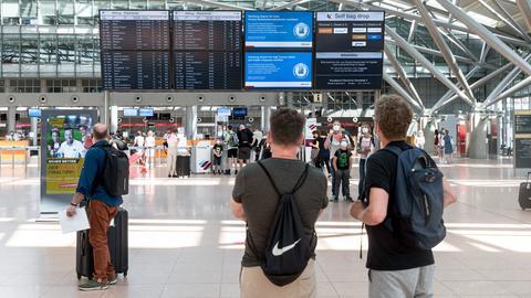 Flugreisende betrachten am ersten Wochenende vor Ferienbeginn in Schleswig-Holstein im Flughafen Hamburg die Abflug-Anzeigetafel. (dpa)