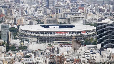"""Ein Banner verkündet auf dem Nationalstadion, einem Austragungsort der Olympischen Spiele und Paralympics in Tokio, unter dem Zeichen der Olympischen Ringe """"Tokio 2020"""". (dpa)"""