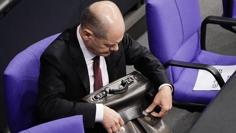 Olaf Scholz packt seine Tasche im Bundestag. (dpa)