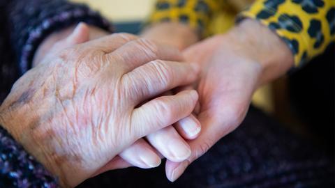 Eine Besucherin einer Pflegeeinrichtung und eine Bewohnerin halten Hände. ()