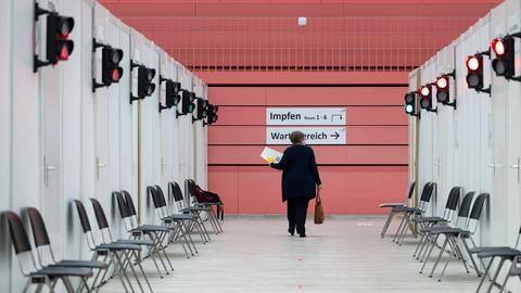 Eine Besucherin geht im Impfzentrum Tübingen durch einen leeren Gang zum Impfen. (dpa)