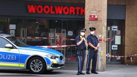 Zwei Polizeibeamte stehen am Tatort vor dem abgesperrten Kaufhaus in Würzburg. ()