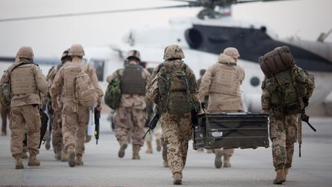 Bundeswehrsoldaten tragen auf dem Flughafen in Masar-i-Scharif zu einem wartenden Hubschrauber eine Feldkiste (Archivbild). (dpa)