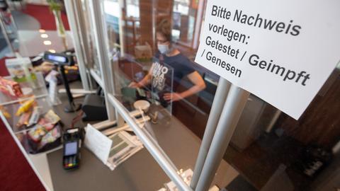 """Ein Schild """"Bitte Nachweis vorlegen: Getestet, Geimpft, Genesen"""" hängt an einer Kasse.  (dpa)"""