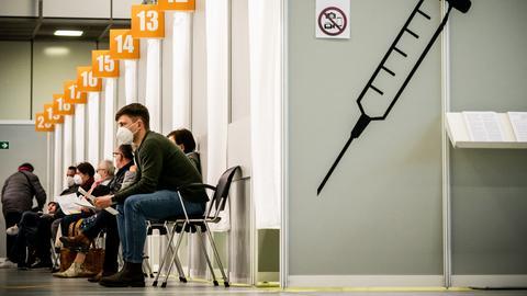 Menschen warten im Corona-Impfzentrum auf dem Messegelände auf ihre Impfung (dpa)