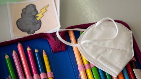 Eine Schutzmaske liegt auf einer Federtasche in einer Schule. (dpa)