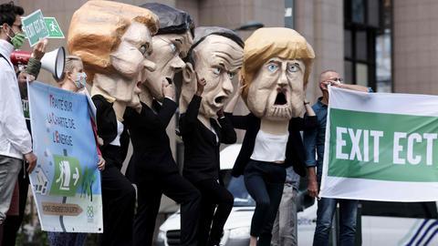 Klimaaktivisten mit Masken der EU-Politiker Ursula von der Leyden, Mark Rutte, Emmanuel Macron und Angela Merkel  (AFP)