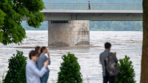 Passanten stehen Abend am teilweise überfluteten Ufer des Inn in Passau (dpa)