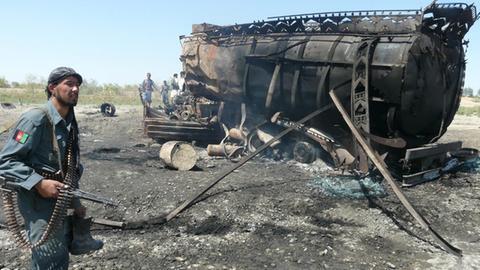 Soldat vor ausgebranntem Tanklastwagen (dpa)