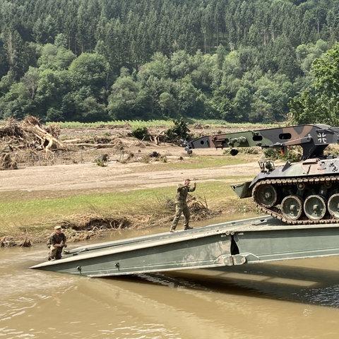 Einsatzkräfte der Bundeswehr bauen eine Behelfsbrücke über die Ahr im Weinort Rech im Landkreis Ahrweiler. Dort hatte in der Nacht zum 15. Juli das Hochwasser schwere Schäden angerichtet und Brücken weggerissen.  (dpa)