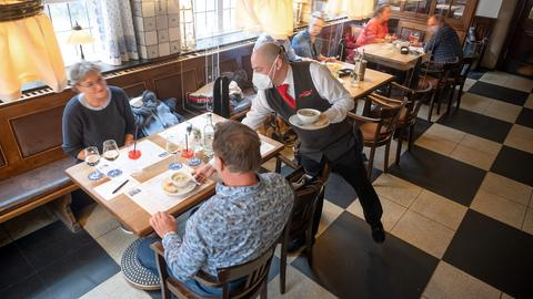Gäste bekommen in einem Gasthaus das Essen serviert. (dpa)