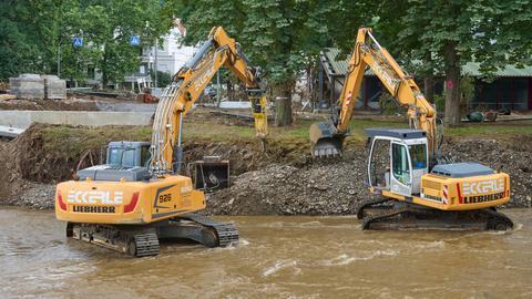 Bagger reißen Teile einer durch die Flut zerstörte Brücke über der Ahr ab. (dpa)