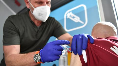 Ein Arzt in einem Impfzentrum injiziert einem Mann Impfstoff. (dpa)
