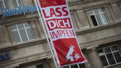 """""""Lass Dich impfen"""" steht auf einer Fahne während einer Corona-Impfaktion der Stadt Köln vor dem Hauptbahnhof (dpa)"""