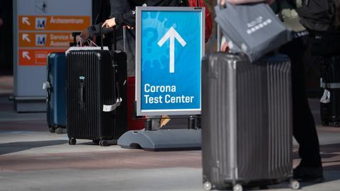 Reisende mit Koffern stehen vor einem Corona-Testzentrum auf dem Flughafen in München an. (dpa)