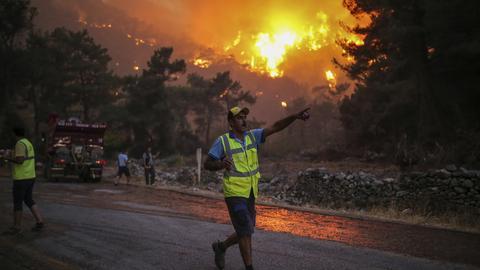 Ein Feuerwehrmann zeigt auf ein Feuer, das im Dorf Cokertme in der Nähe von Bodrum in der Türkei wütet. (dpa)
