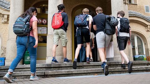 Schüler betreten den Eingang zum Rheingau Gymnasium. (Archivbild: August 2020) (dpa)