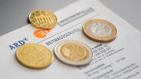 Euromünzen liegen auf einem Anschreiben zur Anmeldung für die Rundfunkgebühren (dpa)