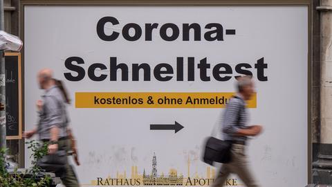 """Passanten gehen an einem Plakat mit der Aufschrift """"Corona-Schnelltest - kostenlos und ohne Anmeldung"""" vorbei. (dpa)"""