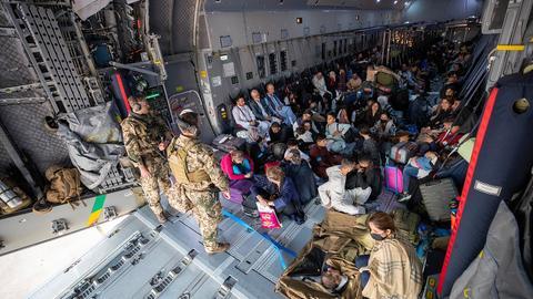 Aus Afghanistan geflohene Menschen sitzen in einer Transportmaschine der Luftwaffe. ()