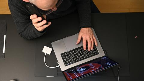 Mann arbeitet am Laptop und telefoniert gleichzeitig (dpa)