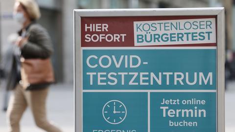 Eine Frau geht an einem Hinweisschild für ein Covid-Testzentrum in Köln vorbei. (dpa)