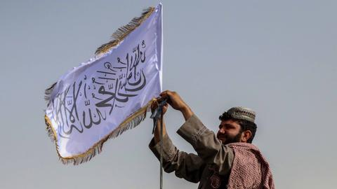 Ein Mann hisst in Kandahar (Afghanistan) die Flagge der Taliban (EPA)