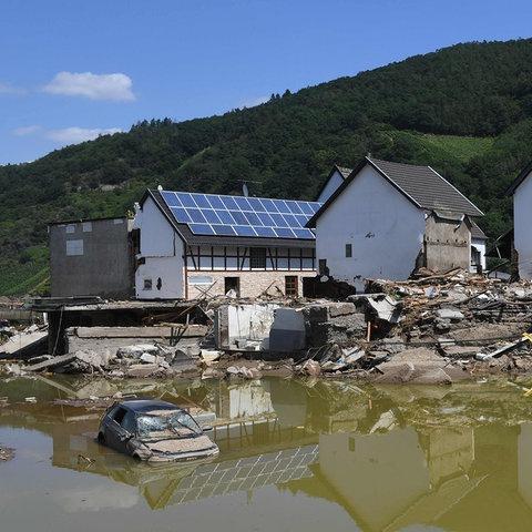 Zerstörte Häuser werden im braunen Hochwasser reflektiert. (AFP)