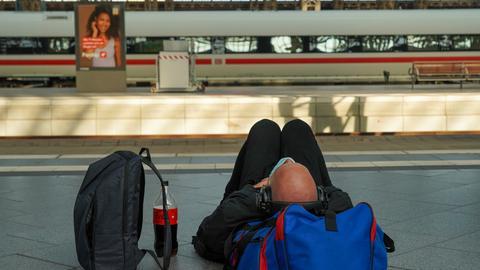 Ein Fahrgast wartet auf dem Bahnsteig in Leipzig schlafend auf einen nach Notfallfahrplan fahrenden ICE der Deutschen Bahn (dpa)