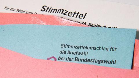 Ein Stimmzettel und ein Umschlag für die Briefwahl liegen auf einem Tisch.  (dpa)