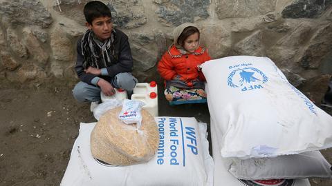 Kinder warten in Kabul (Afghanistan) auf einen Transport, nachdem sie vom Welternährungsprogramm gespendete Lebensmittel erhalten haben.  (AP)