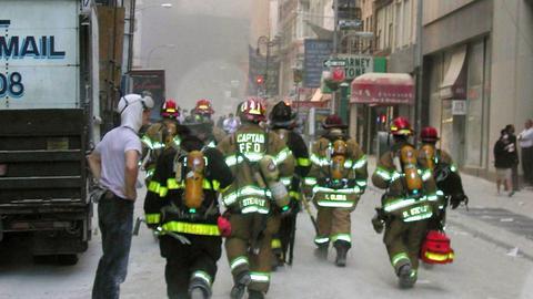 New Yorker Feuerwehrleute am 11.9.2001 auf dem Weg zu den rauchenden Trümmern der World Trade Center (dpa)