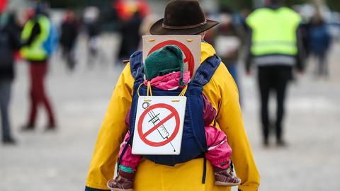 """Eine Teilnehmerin einer Protestkundgebung der Initiative """"Querdenker"""" trägt auf dem Cannstatter Wasen ein Schild gegen Impfungen auf ihrem Rücken. (dpa)"""