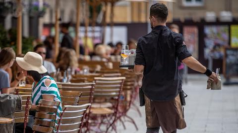 Eine Servicekraft läuft im Außenbereich eines Restaurants an Gästen vorbei. (dpa)